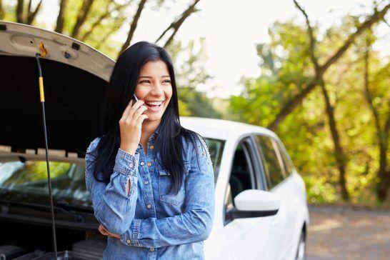 車のトラブル時にロードサービスに電話する女性
