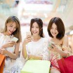 スマートフォンを見るショッピング中の女性