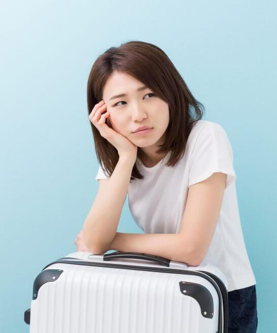 スーツケースで頬杖をつく困った表情の女性 - コピー