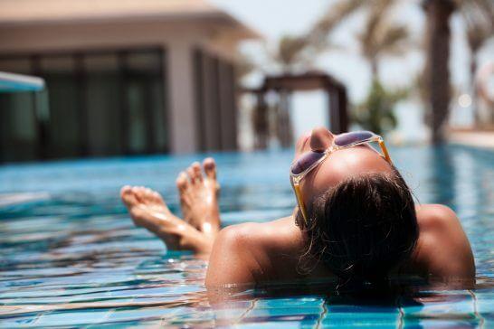 プールでくつろぐリッチな女性