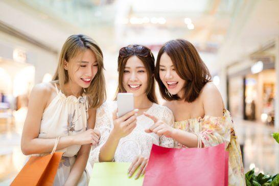 スマートフォンを見るショッピング中の女性 (1)