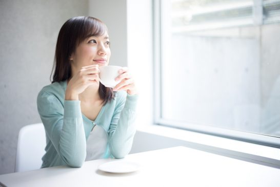 コーヒーを飲んで微笑む女性