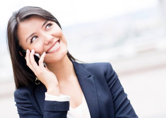 携帯電話で通話するOL