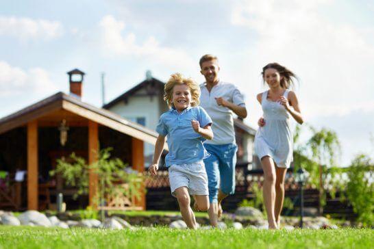 住宅を背景に走る家族