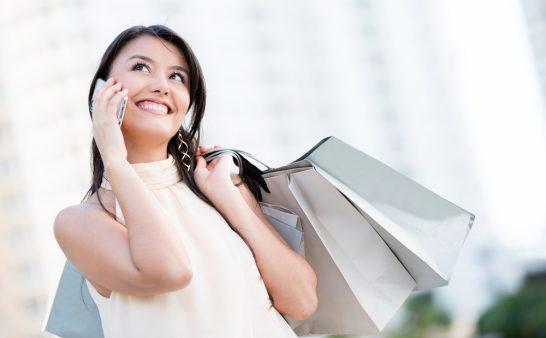 スマホで電話するショッピング中の女性