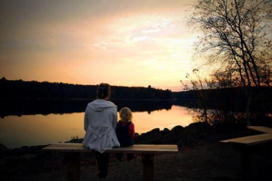 湖のほとりに腰かける親子
