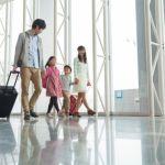 手荷物(スーツケース)を引きずって空港を移動する家族