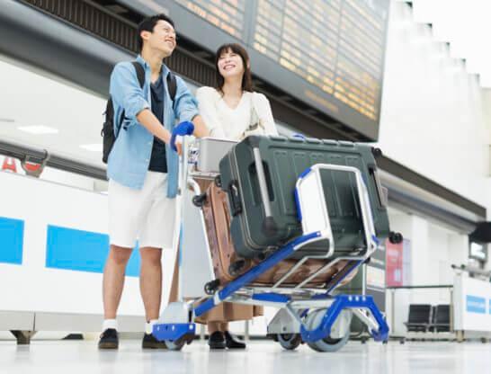 手荷物(スーツケース)のカートを押して空港を移動するカップル - コピー