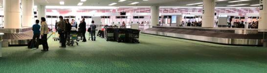 飛行機に預けた手荷物の到着を待っている乗客