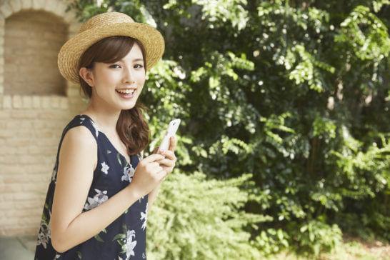 屋外でスマホを操作する笑顔の女性