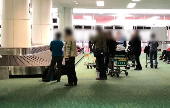 空港で手荷物が出てくるのを待つ人々(手荷物優先受け取りのメリット)