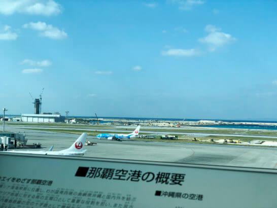 那覇空港の概要の看板と駐機するJALの飛行機