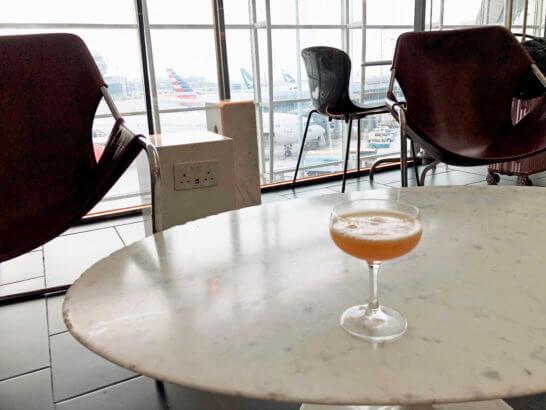 アメックスプラチナと香港センチュリオンラウンジのシグネチャーカクテルを置いたテーブル席