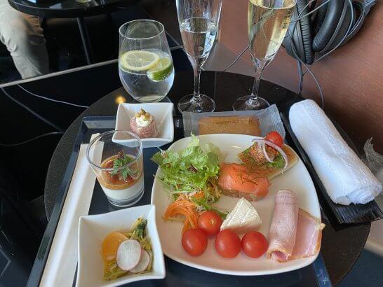 羽田空港ANAスイートラウンジのシャンパン、レモンとライムを入れたペリエ、サラダ、充実の豪華オードブル