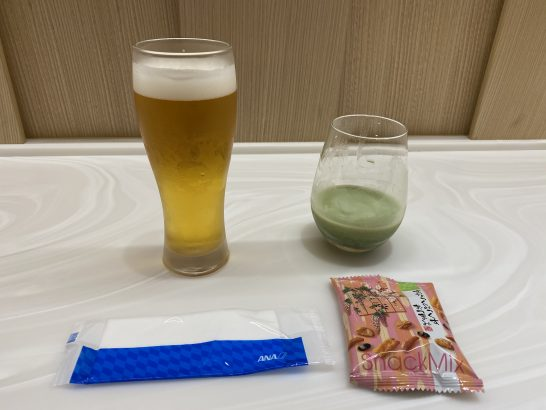 那覇空港ANAラウンジのビール、キューサイ、すなっくミックスおつまみ