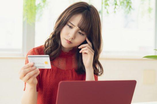 クレジットカードを見てショックを受けて困る考える女性