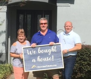 """Matt Mobley and clients Peter and Robin hold a sign saying """"We bought a house!"""" standing in front of their one-story home they purchased."""