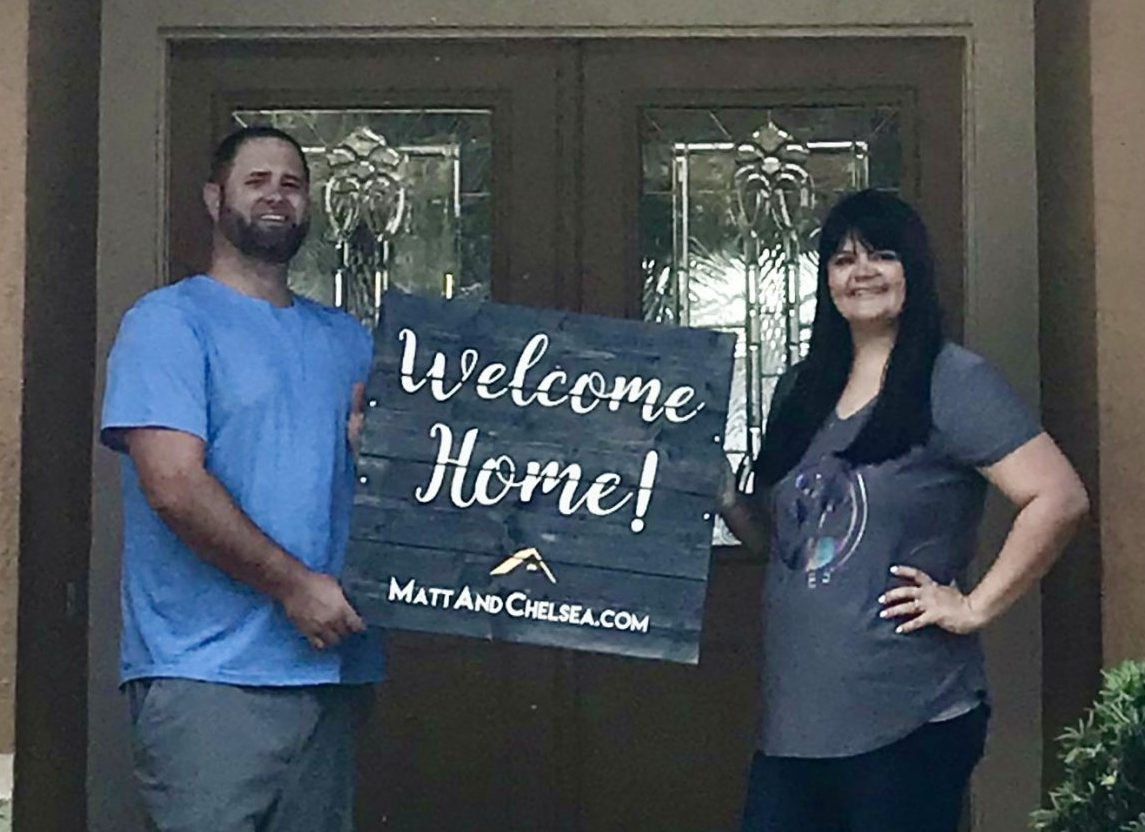 "Matthew and January stand in front of the front door of the home they bought holding the sign, ""Welcome Home!"""