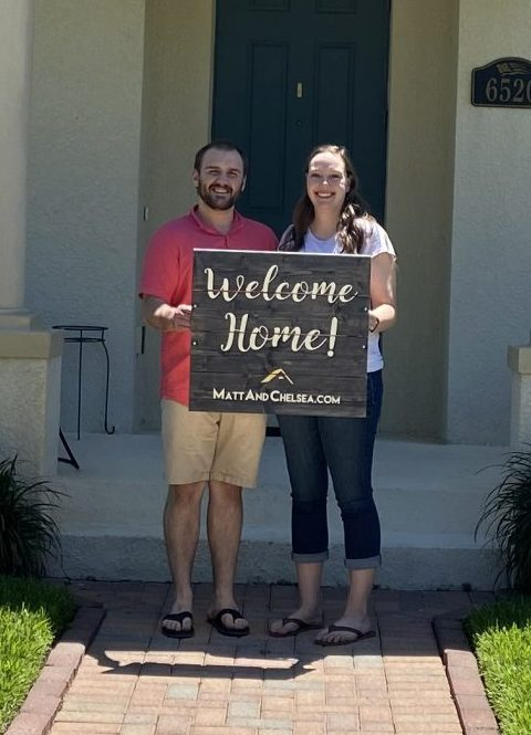 "Adam and Holly stand in front of the two-story home they purchased holding the sign, ""Welcome Home!"""
