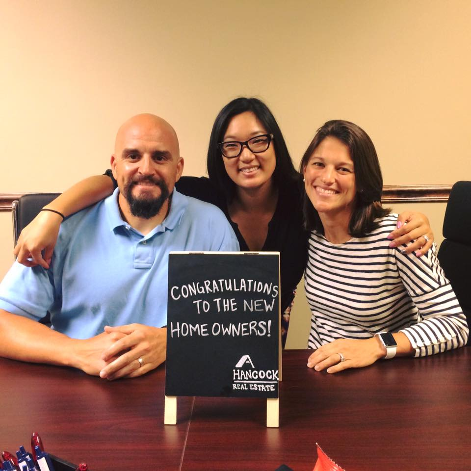 """Photo of agent Chelsea Eckert and clients Mike and Krissy with a sign saying """"Congratulations to the new homeowners!"""""""