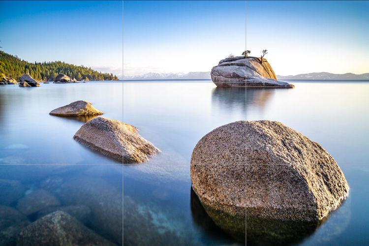Long exposure of Bonsai Rock, Lake Tahoe, at sunset. The water has a milky white texture and the rocks are bathed in warm yellow glow.