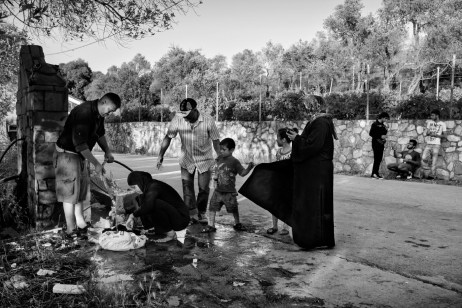 Some Syrian asylum seekers are washing their clothes in a fountain while others are waiting to collect drinking water or have a wash. There is no food, water or bathrooms in the makeshift refugee camp where they are hosted. Mytilene, Lesbos, Greece 2015. © Matteo Bastianelli