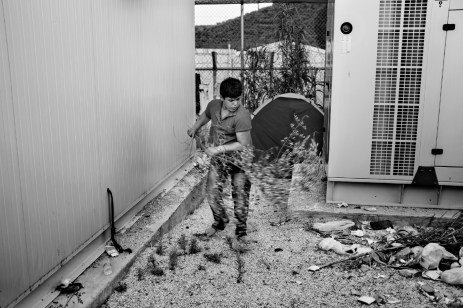 A Syrian guy sweeping the floor around his tent at the makeshift refugee camp of Moria, using a tree branch as a broom. Moria, Lesbos, Greece 2015. © Matteo Bastianelli