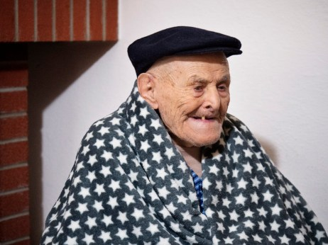 107-year-old Giuseppe Ignazio Boi at home in front of his fireplace. A huge fan of the Cagliari football team: Giuseppe cannot see well anymore, nevertheless, he still listens to football matches on the radio. Dolianova, Italy 2015. © Matteo Bastianelli
