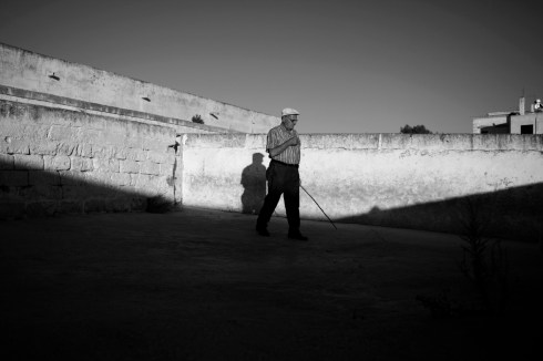 Mr. Fornaro is seen walking in a empty sheepfold, inside his farmhouse. He lost his wife to cancer and it was here, in 2008, that an order to slaughter around 700 sheep that were infected with dioxin was carried out. Taranto, Italy 2013. © Matteo Bastianelli