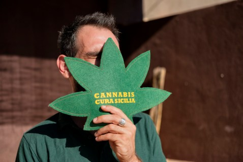 """34-year-old Alessandro Raudino, affected by multiple sclerosis and cannabis user for therapeutic purposes, hides his face with a symbol of the """"Cannabis Cura Sicilia"""" association, of which he is the founder. Modica (Ragusa), Italy 2016. © Matteo Bastianelli"""