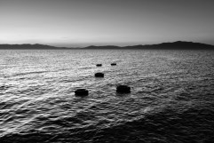 Five ring buoys left in the water by migrants who survived a perilous sea crossing from the Turkish coast of Dikili to the Greek island. Six people died at sea two days previously. Kratigos, Lesbos, Greece 2015. © Matteo Bastianelli