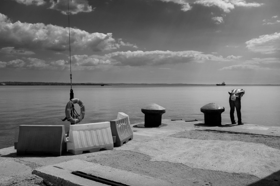 A man looking down into the sea from the pier. Thessaloniki, Greece 2015. © Matteo Bastianelli