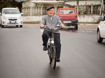 101-year-old Giulio Podda is seen riding his bicycle through the streets of the village. Passionate about writing and theatre, Giulio rides his bicycle everyday for at least 3 km. San Sperate, Italy 2015. © Matteo Bastianelli