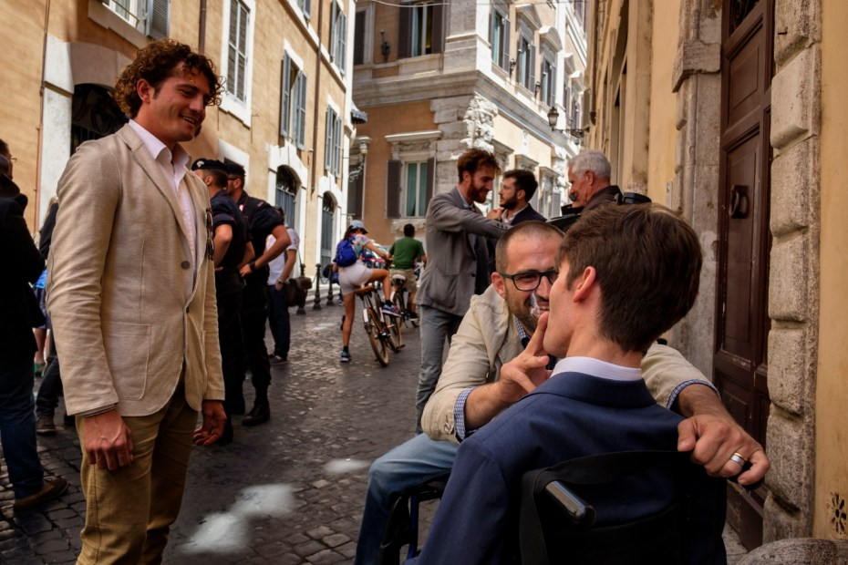"""Andrea Trisciuoglio, affected by multiple sclerosis and co-founder of the first Italian cannabis social club """"LapianTiamo"""", is seen helping his quadriplegic friend Alberico Nobile smoke his Bedrocan therapy in front of some Carabinieri and passers-by in the vicinity of the Chamber of Deputies. They both use medical cannabis, provided by Apulia's public healthcare service free of charge. Rome, Italy 2016. © Matteo Bastianelli"""