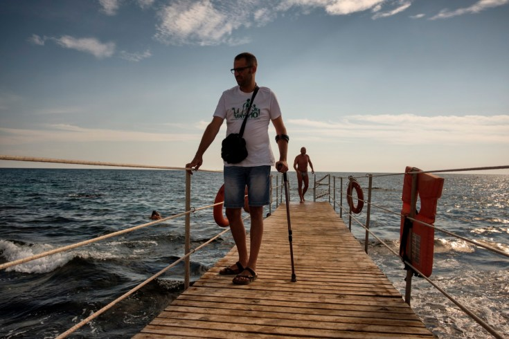 """38-year-old Andrea Trisciuoglio, affected by multiple sclerosis, walks on a pier near the sea. Andrea is one of the founder members of """"LapianTiamo"""", the first Italian cannabis social club, the aim of which is to enable patients to heal with medical cannabis. Torre San Giovanni (Lecce), Italy 2016. © Matteo Bastianelli"""