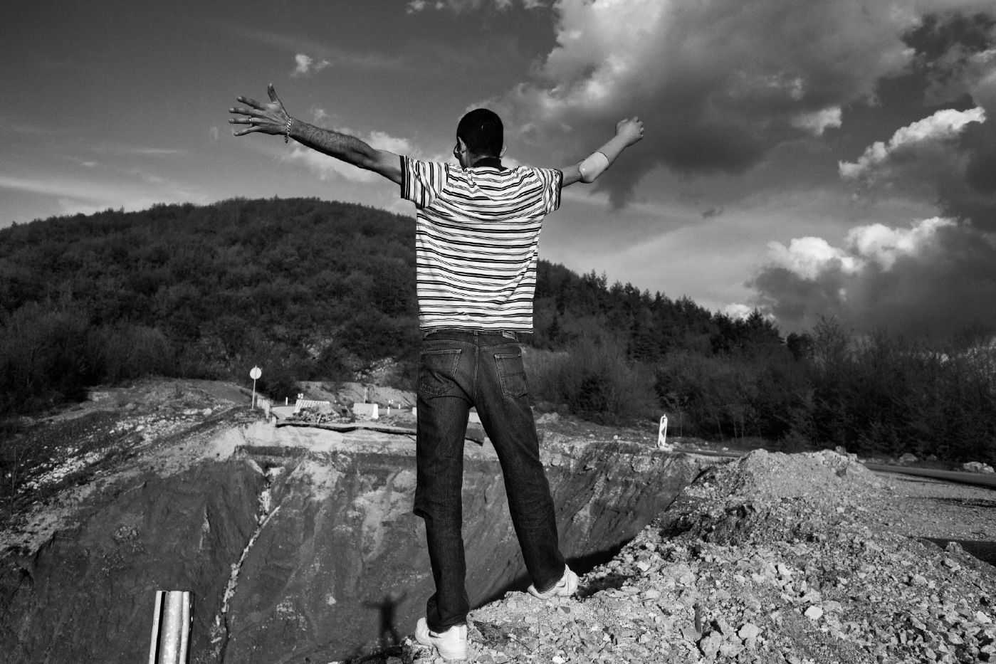 Adis Smajić, 32-year-old, looks at his shadow on the bottom of a collapsed street. Adis was 13 years old when he had an accident on a land mine. Since one year he became father and now he is living the best time of his life. Sarajevo, Bosnia and Herzegovina, 2014. © Matteo Bastianelli