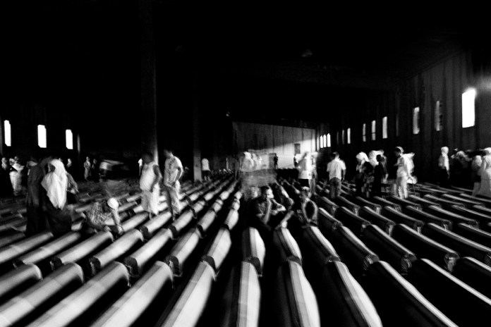 Families of the victims beside the remains of their loved ones, contained in the 775 coffins lined up inside the UN headquarters, home to the soldiers who had the task of protecting the population of Srebrenica. Potočari, Serb Republic of Bosnia and Herzegovina, 2010. © Matteo Bastianelli