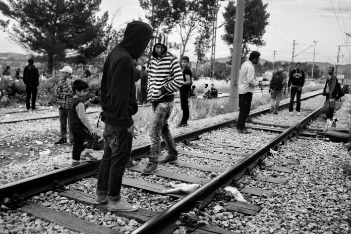 Some asylum seekers looking at a dog just hit by a train. Many people have died in the same way, walking along the railway tracks to reach the Republic of North Macedonia. Idomeni, Greece 2015. © Matteo Bastianelli