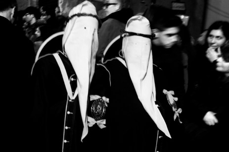 "Two members of the Confraternity of Mysteries during the procession in Holy Week. The ""perduni"", members of the Confraternity with their hoods pulled low over their eyes, walk slowly, swaying on their legs for about 13 hours until their return to the church. Taranto, Italy 2013. © Matteo Bastianelli"