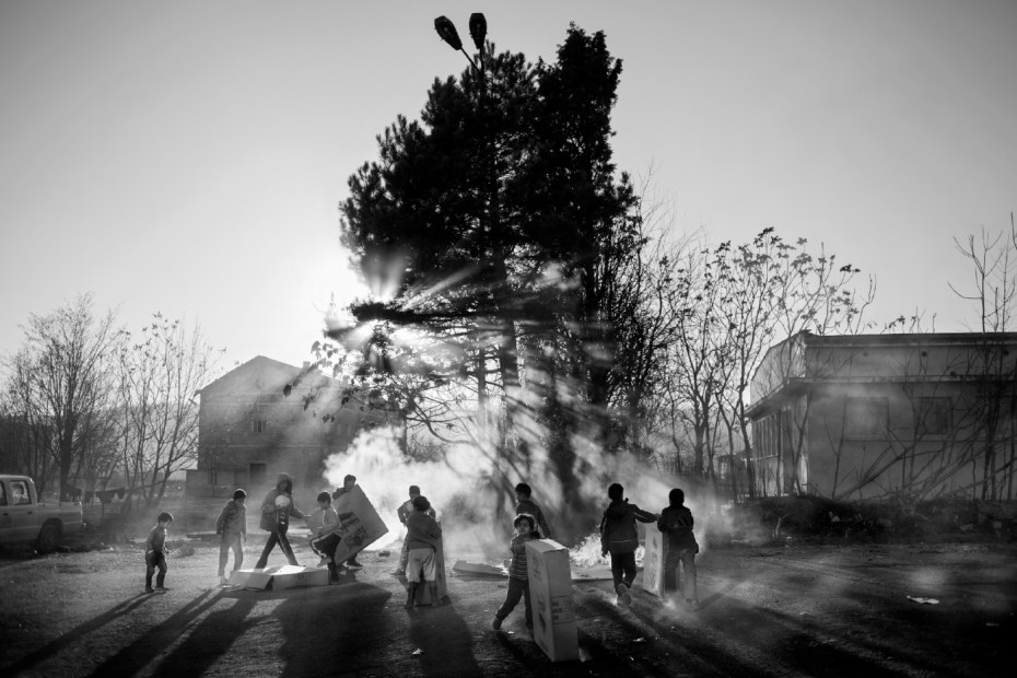 Syrian children light a fire to warm up at the former military base where a refugee camp was set up to cope with the humanitarian emergency of asylum seekers fleeing the Syrian Civil War. Harmanli, Bulgaria 2013. © Matteo Bastianelli