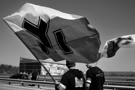Two youths hold a flag displaying an ancient Bulgarian symbol, well liked by young Nazis, during a protest against the presence of refugees in Harmanli, Bulgaria 2014. © Matteo Bastianelli
