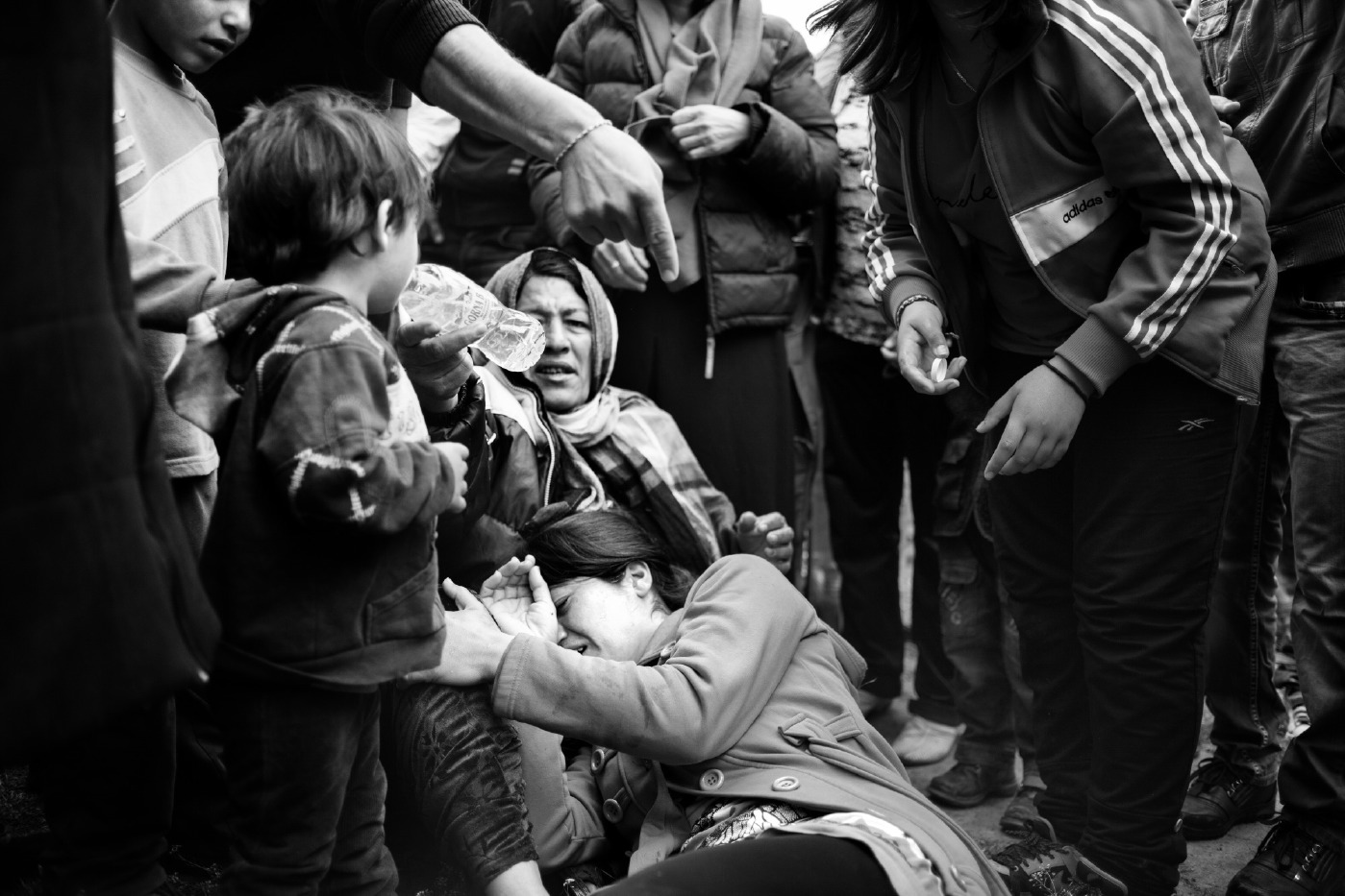 A girl lies on the ground in her mother's arms after she was hit by a policeman during clashes between the police force and refugees. The asylum seekers organized a protest after an official visit of the former European Commissioner for Home Affairs, Mrs. Anna Cecilia Malmstrom, when she explained that with their Bulgarian documents they would not be able to leave Bulgaria, according to the Dublin Regulation. Harmanli, Bulgaria 2014. © Matteo Bastianelli