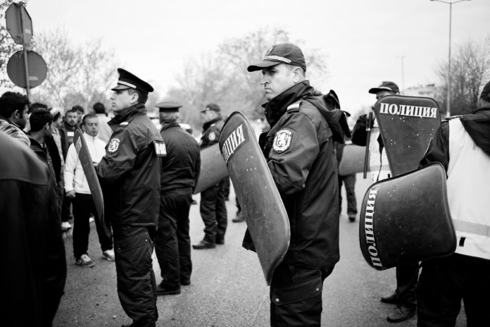 Police line up in front of a group of Syrian refugees. The asylum seekers organized a protest after an official visit of the former European Commissioner for Home Affairs, Mrs. Anna Cecilia Malmstrom, when she explained that with their Bulgarian documents they would not be able to leave Bulgaria, according to the Dublin Regulation. Harmanli, Bulgaria 2014. © Matteo Bastianelli