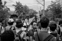 A group of refugees tries to cross the border between Greece and the Republic of North Macedonia walking along the railway tracks while a border policeman orders them to go back to Greece. Republic of North Macedonia 2015. © Matteo Bastianelli