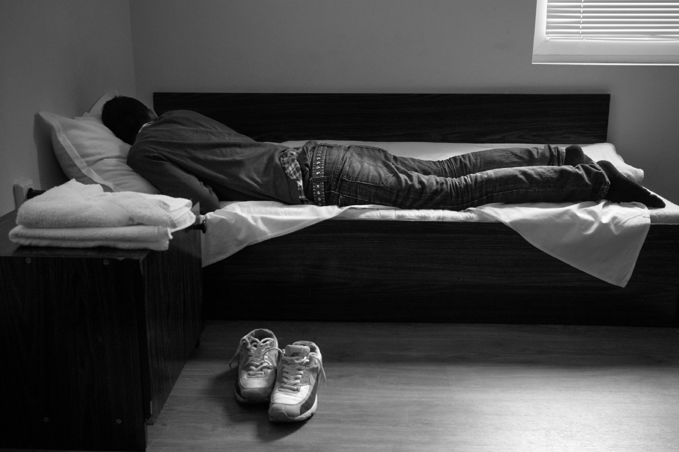 21-year-old Syrian refugee Mohamad Al Masalmeh rests in a hotel room in Sofia before to continue his journey through Romania. Sofia, Bulgaria 2014. © Matteo Bastianelli