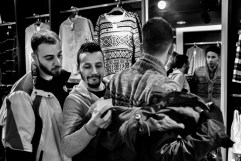 23-year-old Syrian refugee Mohamad Al Masalmeh wearing a coat in a shopping mall, while his cousin Hani and their friend Hassan check the price tag. Lippstadt, Germany 2016. © Matteo Bastianelli