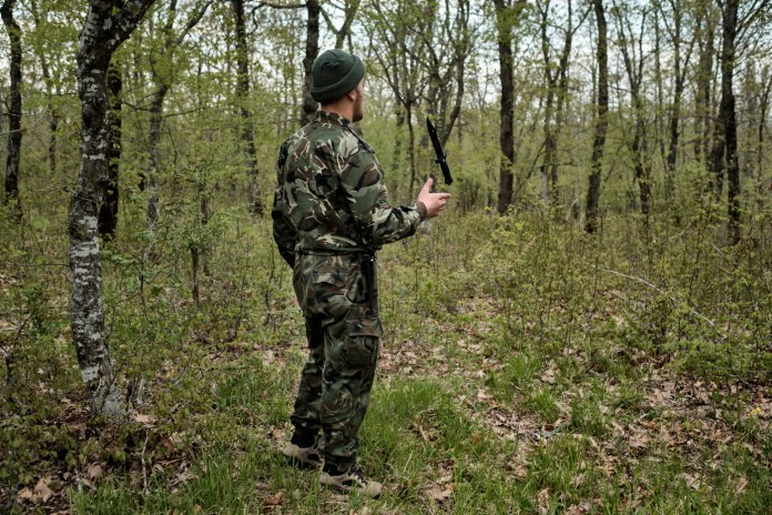 "A volunteer from the ""Vasil Levski"" Bulgarian Military Veterans Union plays with a knife while surveilling the forest. Yasna Polyana, Bulgaria 2017. © Matteo Bastianelli"