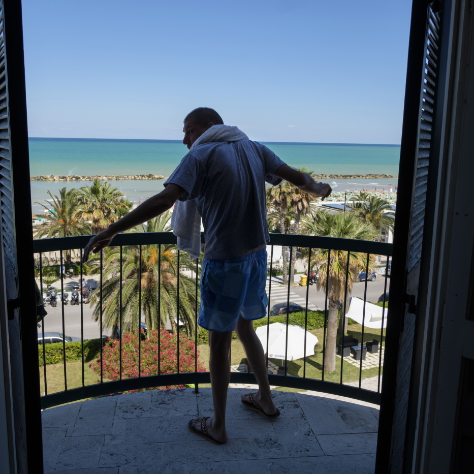 39-year-old Pierluigi Giorgi is seen on the balcony of the hotel room where he has been staying after losing his home in Arquata del Tronto, following the earthquake of 24 August 2016. Grottammare, Italy 2017. © Matteo Bastianelli