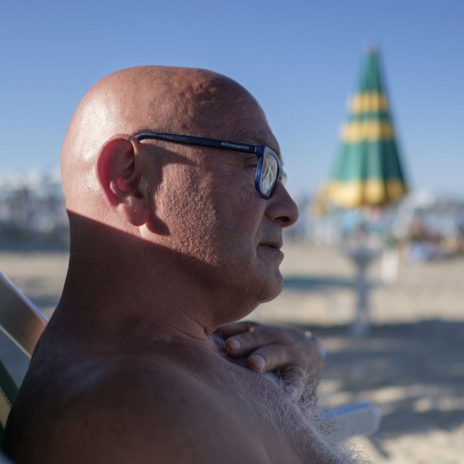 Domenico is seen relaxing on the beach in front of the hotel where he is temporarily staying. Grottammare, Italy 2017. © Matteo Bastianelli
