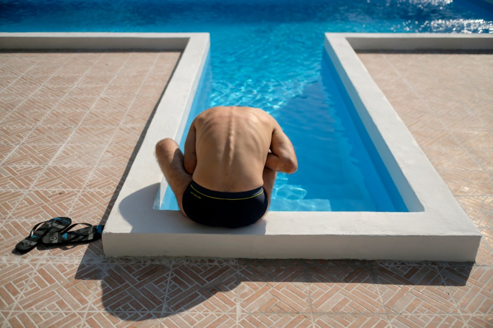 """34-year-old Alessandro Raudino, affected by multiple sclerosis and founder of the """"Cannabis Cura Sicilia"""" association, is seen by his uncle's pool. Lentini (Siracusa), Italy 2016. © Matteo Bastianelli"""